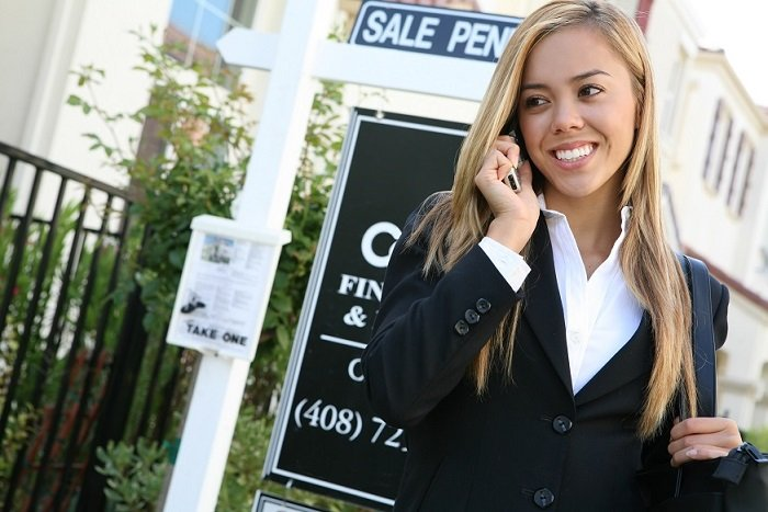 woman realtor in front of sale sign