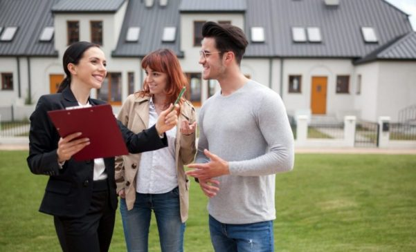 Young couple with real estate agent in front of house
